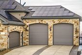 Home Exterior With Beautiful Stone Wall And Solar Panels On The Roof poster