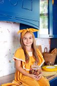 Little Girl In A Yellow Dress Holds A Jar Of Raw Pasta On The Background Of The Kitchen At Home. Lit poster