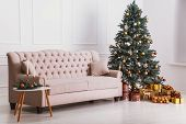 Beautiful Beige Sofa, Christmas Tree With Decorations And Gifts, A Table With Candles. Cozy Christma poster