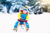 Little Boy Enjoying A Sleigh Ride. Child Sledding. Toddler Kid Riding A Sledge. Children Play Outdoo poster