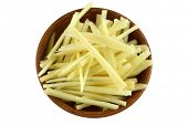 A wooden bowl full of thin julienne strips of ginger rhizome root