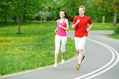 Young fitness man and woman doing jogging sport outdoors