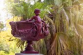 Cupid Flowerbed Sculpture. Roman Flower Pot, Vase With Sculptures In The Botanical Garden Of Porto,  poster