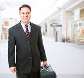 Fotografia de um empresário, segurando sua mala e caminhar através do saguão do aeroporto.