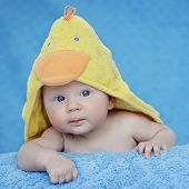 Curious, happy, three months old baby posing on blue blanket with yellow towel