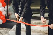 Businessman Cutting Red Ribbon With Pair Of Scissors. Two Man In A Classic Black Official Suit Cuts  poster
