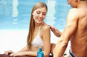 Young man lubing back of attractive woman in pool with sunscreen