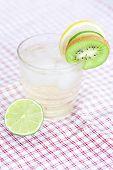 Wasser mit Zitrone und Limone, Kiwi in ein Glas mit Eis