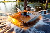 stock photo of shadoof  - Old flooding well and a sweep or shadoof with timber bucket at golden sunlight - JPG
