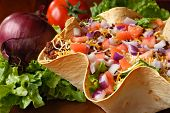 Taco salad in freshly baked flour tortilla bowl (seasoned ground beef, lettuce, onions, tomatoes, an