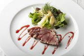 stock photo of yellowfin tuna  - grilled tuna steak on a plate with salad - JPG