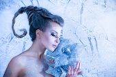 Beautiful sexy, glamorous girl with drawings on the body in an image of the queen of winter. Blue to