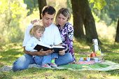 stock photo of scriptures  - young family read the Bible in nature - JPG