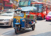 BANGKOK - FEBRUARY 20: Tuk-tuk moto taxi on the street in the Chinatown area on February 20, 2012 in Bangkok. Famous bangkok moto-taxi called tuk-tuk is a landmark of the city and popular transport.