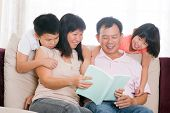 Southeast Asian family living lifestyle. Parents and children reading books at home.
