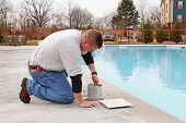 stock photo of cleaning service  - Service man cleaning pool filters removing leaves that have fallen in pool this fall - JPG