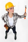 Angry looking female builder wielding hammer in the air