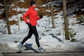 Runner, spring running, exercise woman. Jogging on early spring in mountains. Healthy lifestyle concept.
