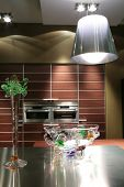 picture of dutch oven  - interior to modern kitchen in brown tone with glass vase and lampshade - JPG