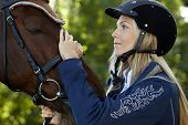 foto of caress  - Pretty female rider caressing horse forehead with love - JPG