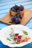 Italian delicacies, starter - figs, prosciutto, gorgonzola and rucola