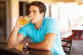 thoughtful young man drinking beer at the bar