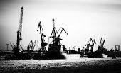 Silhouettes Of Cargo Port Skyline With Cranes, Ships And Poles