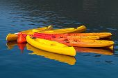 Bright Yellow And Red Canoes Moored With Buoy On Still Water