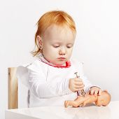 little girl playing doctor with a doll