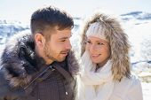 Close-up of a smiling young couple in fur hood jackets against snowed mountain range