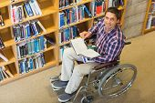 High angle portrait of a man in wheelchair reading a book in the library