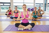 Portrait of fitness class and instructor sitting in Namaste position on exercise mats