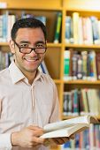 Portrait of a smiling mature student reading book against bookshelf in the library
