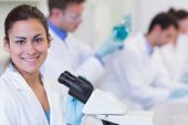 stock photo of coat tie  - Portrait of a smiling female with researchers working on experiments in the laboratory - JPG