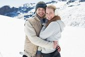 Portrait of a loving young couple in warm clothing on snow covered landscape