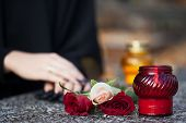 foto of grieving  - Woman in mourning arranging flowers and candles on the gravestone - JPG