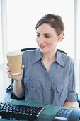 Cute businesswoman looking at disposable cup sitting at her desk in the office