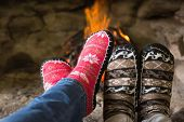 Close-up of romantic couple's legs in socks in front of fireplace at winter season at home