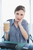 Tired casual businesswoman holding a disposable cup while sitting at her desk and looking at camera