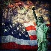 stock photo of memorial  - Composite photo of the statue of Liberty with a flag and fireworks in the background - JPG