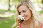 Beautiful blonde woman smelling a flower sitting in a park smiling at camera