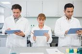 Group of serious scientists using tablet PCs in the laboratory