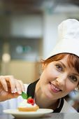 Smiling head chef putting mint leaf on little cake in professional kitchen