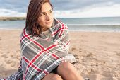 Beautiful  young woman covered with blanket at the beach