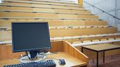View of computer monitor with empty wooden seats with tables in a lecture hall