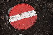 Round Steel Sewer Manhole With Painted Red Stop Sign On It