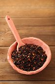 chipotle - jalapeno smoked chilli flakes in pottery bowl,  shallow dof