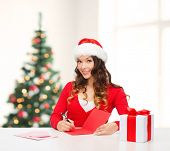 christmas, x-mas, gifts, presents, celebration concept - smiling woman in santa helper hat with gift box and postcard