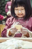 Portrait of little girl making dumplings in traditional clothing