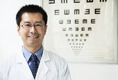 Portrait of smiling optometrist with eye chart in the background